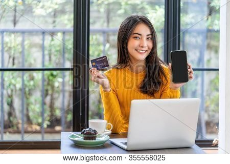 Young Asian Woman Using Credit Card And Presenting Mobile Phone For Online Shopping In Coffee Shop O