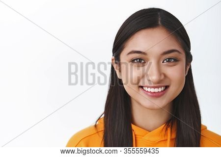 Headshot Of Beautiful Smiling Healthy Asian Girl In Orange Hoodie, Grinning Delighted And Looking Ca