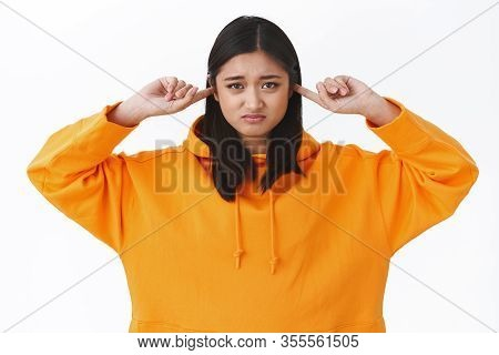 Waist-up Portrait Gloomy And Sulking Young Asian Woman In Orange Hoodie, Grimacing And Pursing Lips,