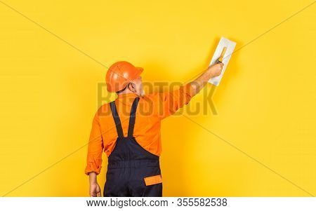 Plasterer In Working Uniform Plastering Wall Indoor. Man With Spatula. Process Of Applying Layer Of