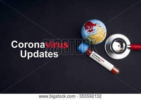 Covid-19 Updates Text With Stethoscope, World Globe And Blood Sample Vacuum Tube On Black Background