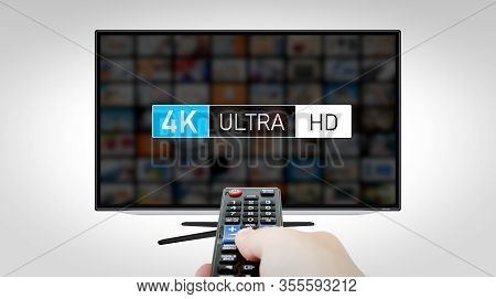4k High Resolution Television. Tv Multimedia Concept. Hand With Remote Control