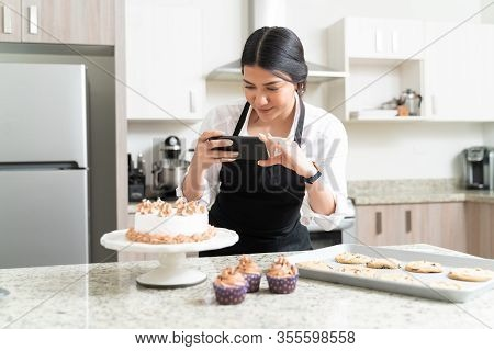 Beautiful Female Food Photographer Taking Pictures Of Cake From Smartphone For Social Media In Kitch