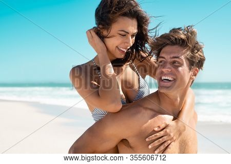 Happy mid man giving piggyback ride to smiling woman at the beach. Guy giving his girlfriend piggyback ride and having fun at beach in the sunshine. Man carrying on back young beautiful latin woman.