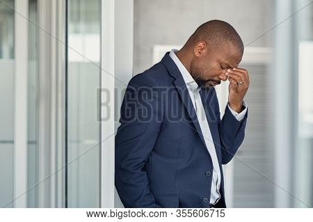 Stressed mature business man rubbing eyes in office. African american businessman in formal feeling tired for fatigue and headache. Depressed and anxious man in office feeling frustrated after layoff.
