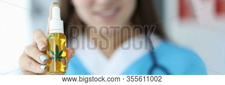 Focus On Female Hand Holding Bottle With Cannabinoid Oil. Beautiful Smiling Lady Wearing Medical Gow