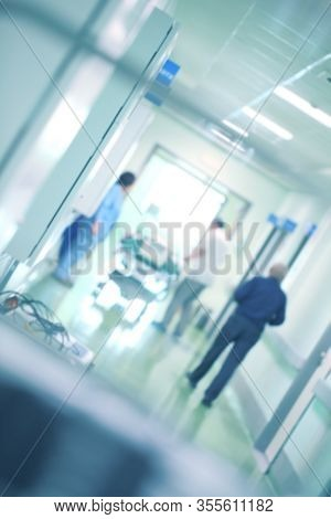 Medical Team Takes Patient On Gurney In Emergency Room, Unfocused Background.