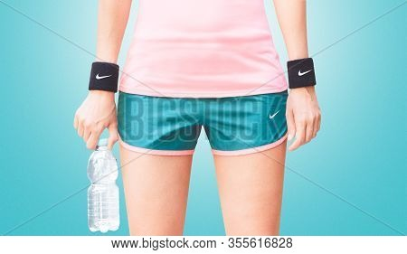 Italy - Young Woman Wearing Nike Sportswear Holding Water Bottle
