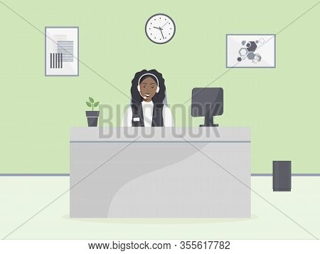 Cozy Call Center Office. Assistant Black Female With Headphones Sitting At Table With Monitor And Ho