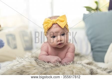 Newborn Baby Girl Posing, With A Twinkle In Her Eyes And Wearing A Bandanna With Yellow Bow. Surroun