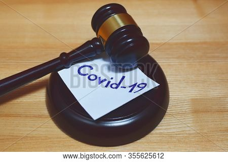 Judges Gavel Or Law Mallet And Word Covid-19 On Sound Block On Wooden Background. Justice, Judgement