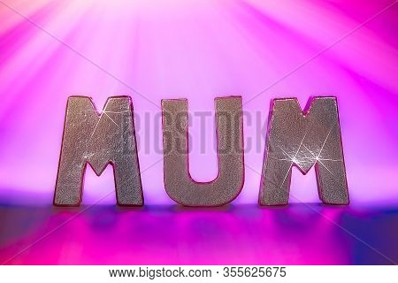 Mums The Word Under Party Pink Disco Lighting. Silver Metallic Text Letters Spelling Mum With Sparkl