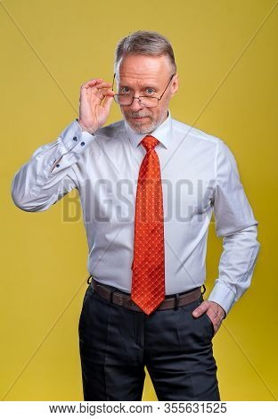 Portrait Of A Senior Man In Glasses. Man Looking At Camera. Business Man In Studio, Yellow Backgroun