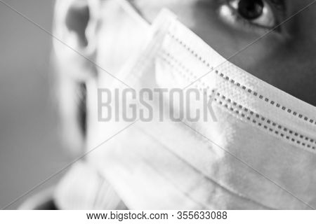 Part Of A Female Face In A Medical Mask. Close-up, Focus On The Mask. Bw Photo.