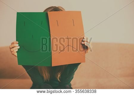Woman With Happy And Sad Face On Paper Sitting On Sofa.