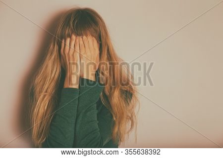 Depressed Woman Standing Alone In Front Of Wall.
