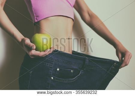 Woman In Large Jeans Holding Apple.weight Loss Concept.