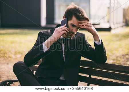 Worried Businessman Using Phone While Sitting Outdoor.