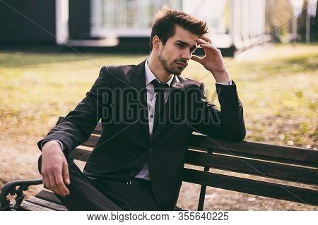 Image Of Elegant Worried Businessman Sitting Outdoor.