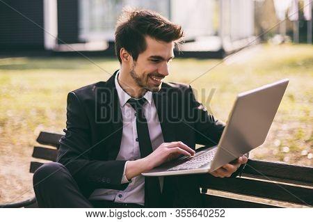 Elegant Businessman Using Laptop While Sitting Outdoor.