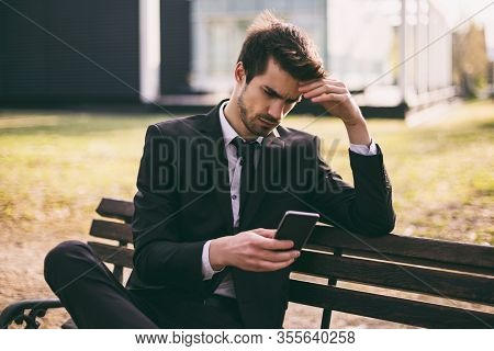 Worried Businessman Using Phone While Sitting Outdoor