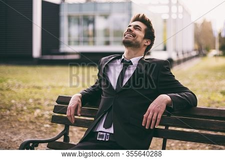 Happy Elegant Businessman Smiling And Enjoys Sitting Outdoor.
