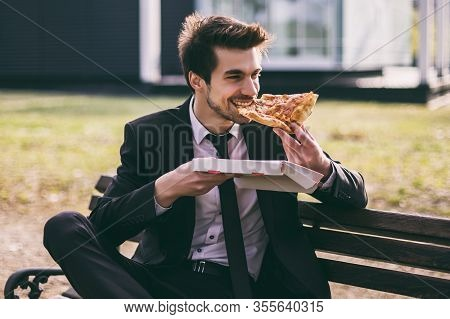 Elegant Businessman Enjoys Eating Pizza On His Lunch Break While Sitting Outdoor.