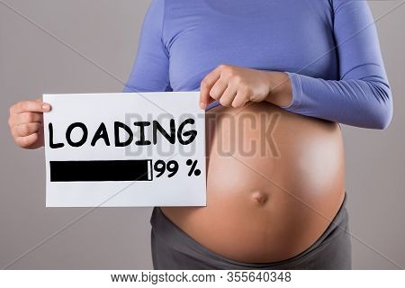 Image Of Close Up Stomach Of Pregnant Woman Holding Paper With Text Loading On Gray Background.
