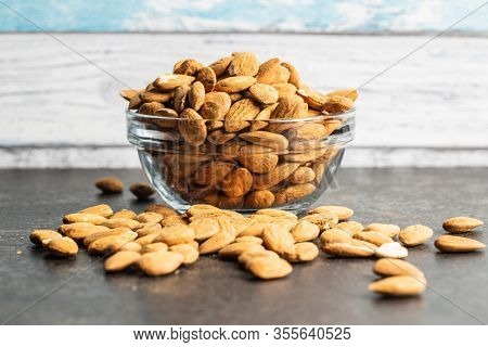 Dried almond nuts in bowl on kitchen table.