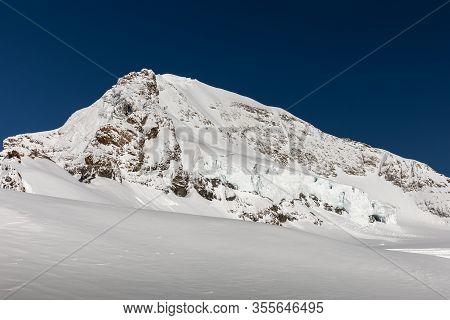 Rock Peak Of Snow-capped Mountain With Blue Sky In Jungfrau, Interlaken, Switzerland. Early Winter O