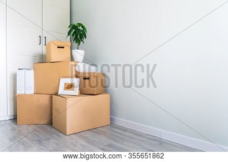 A Lot Of Cardboard Boxes With Things To Move. Check-in To A New Apartment Or Office. Wall And Closet