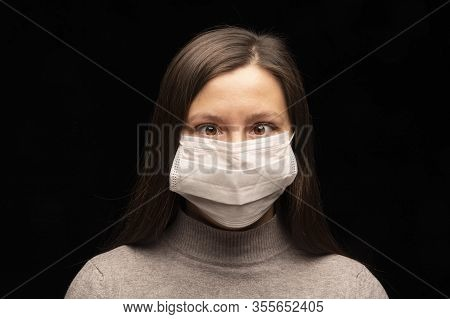 A Young Woman In A White Medical Mask From The Coronavirus Simulates Strabismus. Ignores And Laughs