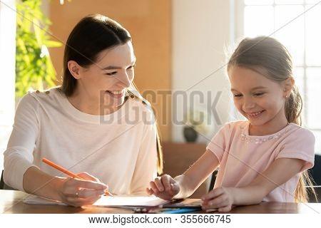 Young Nanny Tutor Educating Little Preschool Child Girl.