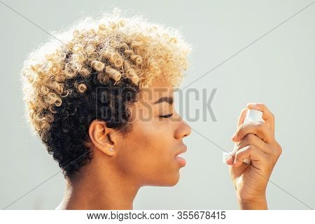 Africa American Woman Using Asthma Inhaler In The Studio White Background