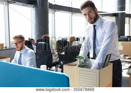 Sad Dismissed Worker Are Taking His Office Supplies With Him From Office