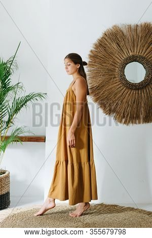 Happy Young Woman In An Ochre Maxi Dress Posing In A Tropical Style Room