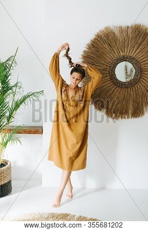 Young Carefree Woman In An Ochre Maxi Dress Posing In A Tropical Style Room