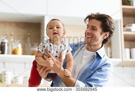 Playing With Daddy. Young Father Raising His Baby Son Like On Plane At Kitchen