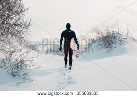 Cold Winter And Male Surfer With Surfboard. Snowy Day With Surfer In Wetsuit.