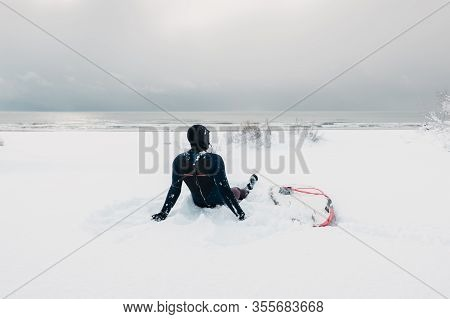 Cold Winter And Male Surfer Relax On Snow With Surfboard. Snowy Day With Surfer In Wetsuit.