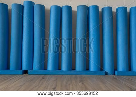 eleven blue rigid foam stem and Pilates rolls standing on wooden oak floor against the white brick wall. Pilates Roll for balance- and stability exercises. Low angle view.