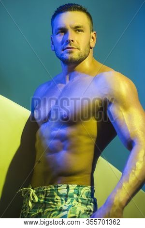 Surfer From Hawaii Posing In The Studio. Surfer Man Going Surfing On Summer Beach.