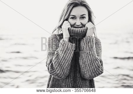 Portrait Of Fashionable Young Blond Woman Posing In High Collar Knitted Sweater On Sea Background. F