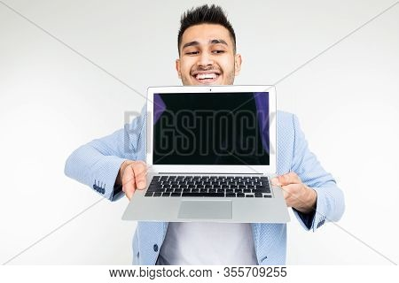 Smiling Young Brunette Man Joyfully Holds A Laptop With Blank For Inserting A Website Page On A Whit