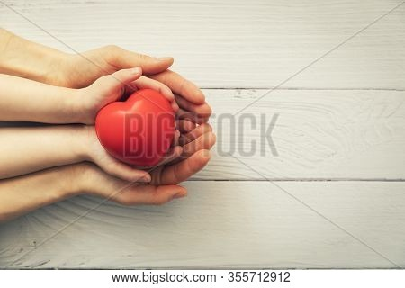 Red Heart In Child And Adult Hands On White Wooden Background. Concept Of Health, Organ Donation, Fa