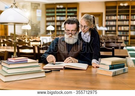 Elderly Man Grandfather And His Granddaughter Reading Exciting Book Together In Vintage Old Library,