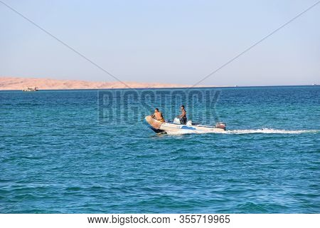 Hurghada / Egypt. 30 July 2018: Two Egyptians Ride Motor Boat On Red Sea. People Ride On Inflatable