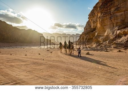Wadi Rum, Jordan - January 31, 2020: Impressive Sky With Sun Rays Over People Riding Camels. Colorfu