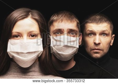 People In Masks That Protect Against Coronavirus. A Woman And Two Men In A Row. The Woman Has A Conf