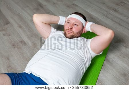 Fat Man Is Exercising His Abdominal Muscles With The Last Of His Strength Lying On The Green Mat On